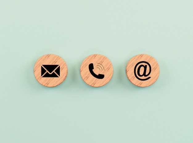 E-mail address ,telephone number and letter icons print screen on circle wooden block on green background for webpage business contact and customer service concept by 3d rendering.