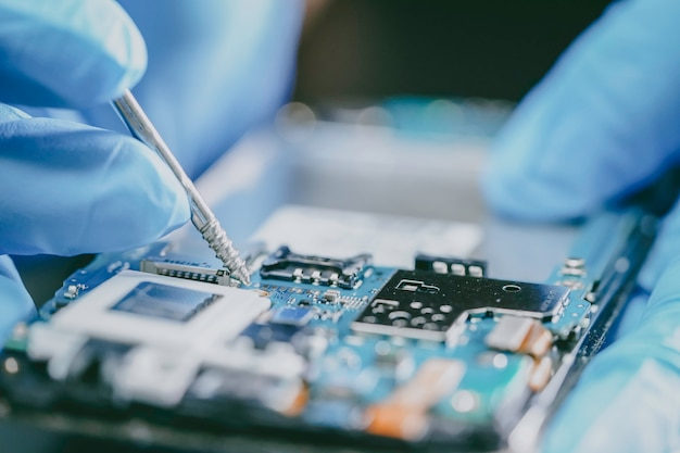 E-waste, technician repairing inside of mobile phone by soldering iron.