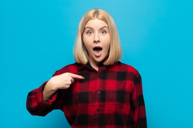 口を大きく開けてショックを受けて驚いた女性が自分を指さしている Premium写真