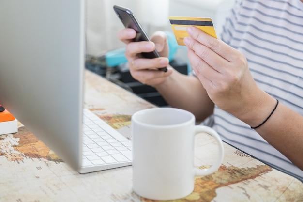 Eコマース、ショッピング、仕事のコンセプト。男の手がクレジットカードを保持し、デスクトップコンピューターと世界地図の作業机の上のホットコーヒーの白いマグカップでモバイルスマートフォンを使用しています。