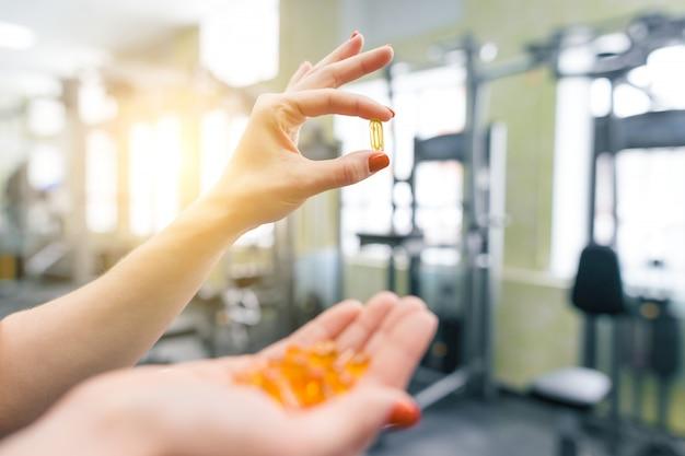 Крупный план рук женщины фитнеса показывая капсулу витамина e