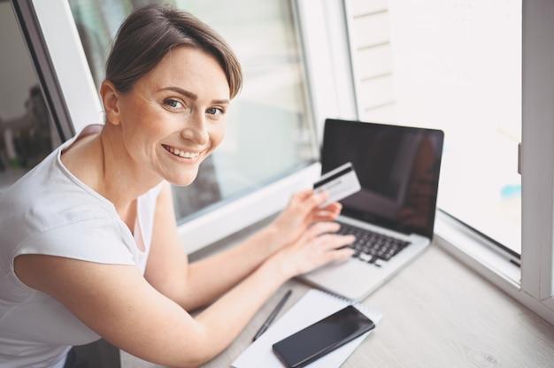 クレジットカードを手で押し、ラップトップコンピューターのキーボードを使用して美しい幸せな女。実業家や起業家が働いています。オンラインショッピング、eコマース、インターネットバンキング、お金の概念を使う