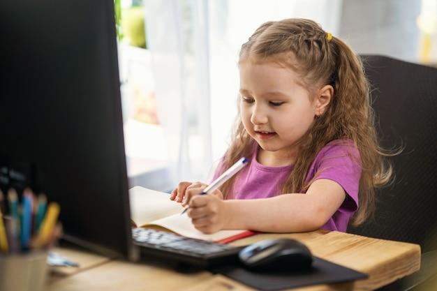 コンピューターをリモートeラーニングに使用しているかわいい女の子がノートに書き込みます