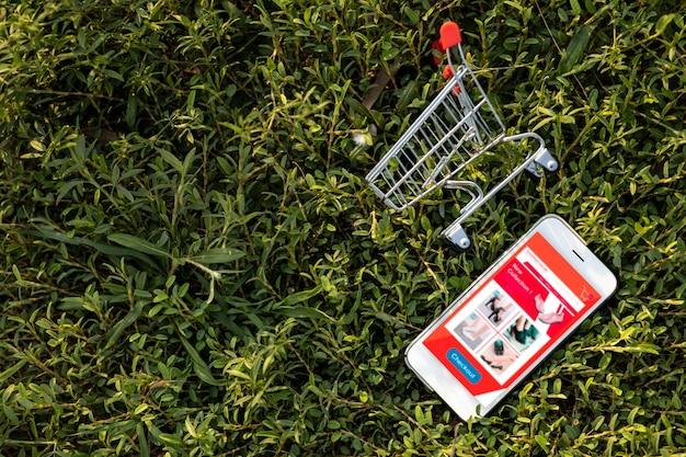 スマートフォンと緑の芝生のショッピングカート。環境のためのウェブサイト上のオンラインショッピングやeコマースのコンセプト。