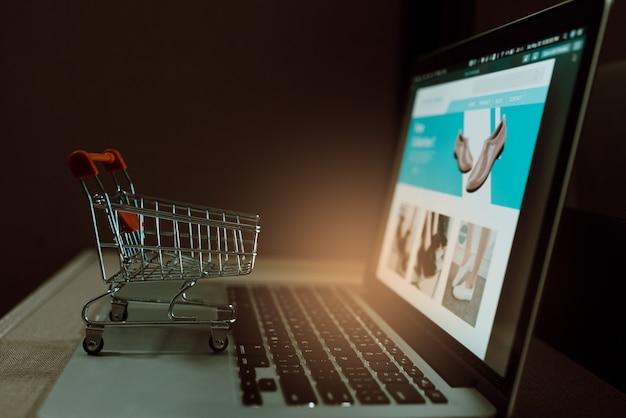 ノートパソコンのキーボードのトロリーショッピングカート。オンラインショッピングまたはインターネットからのeコマースのアイデア。