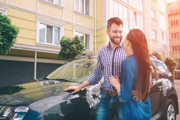 Eは正しい選択をしました。彼のガールフレンドを抱き締めるとキーを押しディーラーで車の近くに立っているハンサムな若い男性