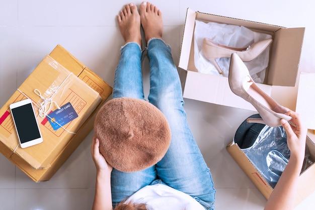 スマートフォン、ファッションアイテム、床にクレジットカードで郵便小包の箱を開けて幸せな女性。オンラインショッピング、eコマース、インターネットバンキングのコンセプトです。上面図。