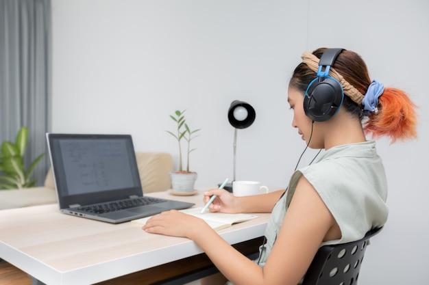 社会的距離の概念のための彼女の家からのラップトップコンピューターでeラーニングで勉強している若い女性。