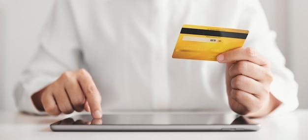 クレジットカードを持ち、タブレットを使用している手、在宅勤務の実業家、オンラインショッピング、eコマース、支出、インターネットバンキング。