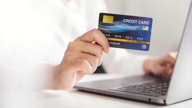クレジットカードを持ち、ラップトップコンピューターを使用している手、在宅勤務の実業家、オンラインショッピング、eコマース、支出、インターネットバンキング。