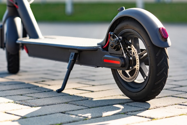 Закройте вверх по взгляду e-самоката припаркованного на тротуаре на городском пейзаже на заходе солнца. модный городской транспорт на современном электрическом самокате. экологичная концепция мобильности.