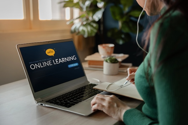 オンラインの概念を学ぶ。コンピューターラップトップを使用して自宅でインターネットからeラーニングコースを学ぶ若い女性