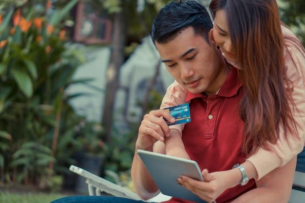 庭に座って、タブレットとダミーのクレジットカードを保持し、現在eコマース経由で製品を購入している幸せな若いカップル。