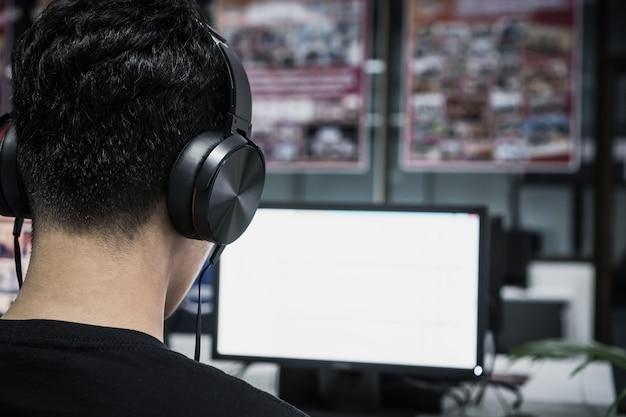 アジアの学生のための教育eラーニング外国語ヘッドフォンを身に着けている若い男