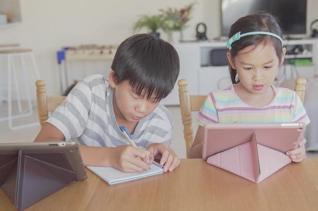 家庭でデジタルタブレットを使用して、ポッドキャスト、ゲーム、オンライン学習教育、eラーニング、ホームスクーリング、社会的距離、分離、ロックダウンの概念を聞いて混合アジアの子供たち