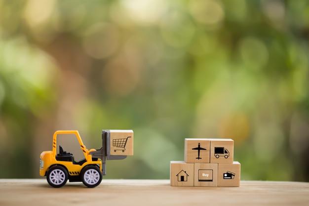 物流ネットワークの分布と貨物貨物の概念:ミニフォークリフトトラックは、アイコン付きの木製ブロックのパレットを移動します。 eコマースで商品や製品を世界中に配送する様子を示しています。