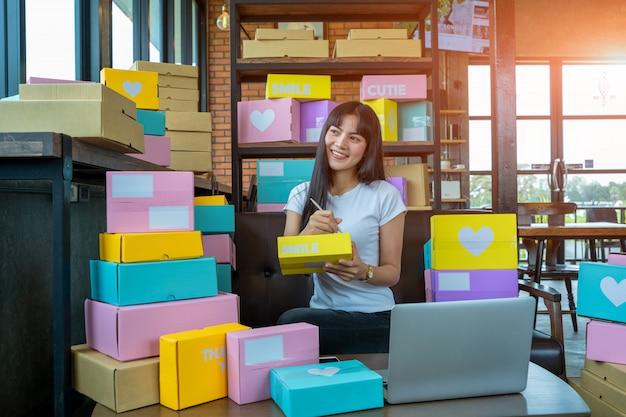 若い女性が顧客、背景、オンライン販売、またはeコマースのホームオフィスパッケージで働いている事業主の新しい注文の後に満足しています。販売の概念。