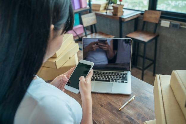 アジアのフリーランスの女性は、顧客への配送、オンライン販売、またはeコマース、販売コンセプトを準備するために、パッケージボックスで製品を準備しています。