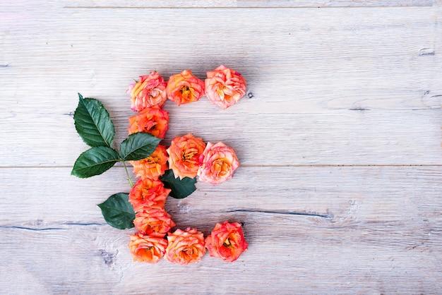E、バラの花のアルファベットは、灰色の木製の背景に、フラットなレイ