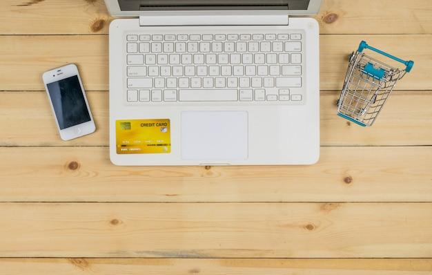 スマートフォン、クレジットカード、木製のテーブルにショッピングトロリーモデルと白いラップトップ。 eコマースショッピング。