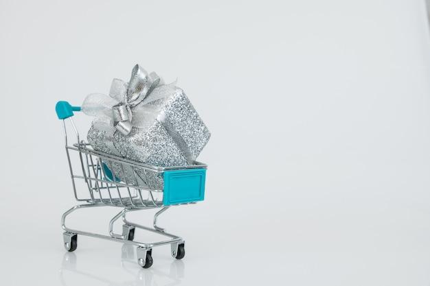 完全にギフトボックスが付いたショッピングカートは、カートに完全に収まり、オンライン購入のeコマースです。