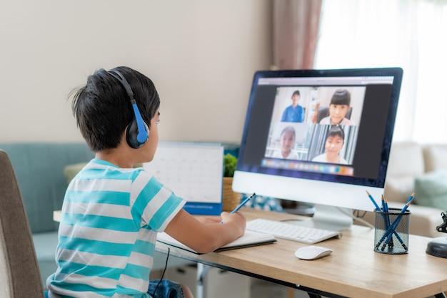 コンピューターでのクラスメートと教師とのアジアの少年学生ビデオ会議eラーニング