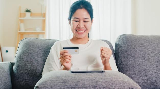 タブレット、クレジットカードを使用してアジアの女性が自宅からリビングルームでeコマースインターネットを購入し、購入します。