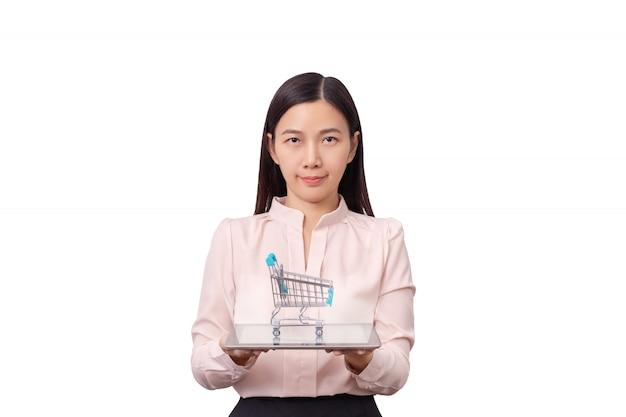 オンラインショッピングとeコマーシャルのビジネスコンセプト。ショッピングカートと一緒に手にタブレットを保持しているアジアの美しい女性