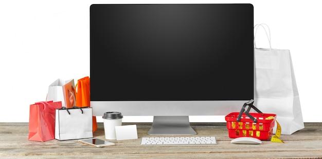 Eコマースのコンセプト。ショッピングアクセサリーとテーブルの上のコンピューターモニター画面