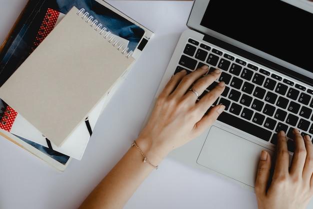 Eラーニングのための白いオフィスの机の上の本のスタックでコンピューターのラップトップを使用して手の平面図、在宅勤務およびワークスペースのコンセプト