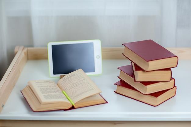 白いタブレットと白いテーブルの上の本。自宅から仕事をしながら自己分離しながらホームオフィス。検疫中のオンライン教育、eラーニング。