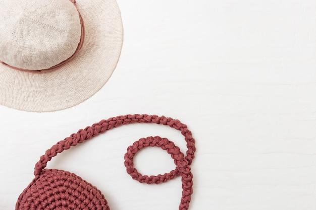 ビーチの女性の帽子と明るいコンクリート背景にピンクの手作りバッグ。上面図。スパをコピーe。