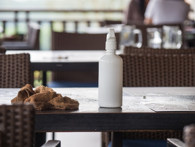 Коричневые столовые салфетки и цилиндр с белой водой помещаются на стол после того, как клиент закончил ea