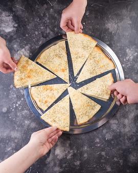 Each person takes a bite of crispy focaccia with mozzarella