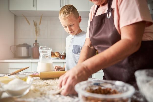 할머니가 쿠키를 만들기 위해 반죽을 반죽하는 모습을 보고 있는 손자