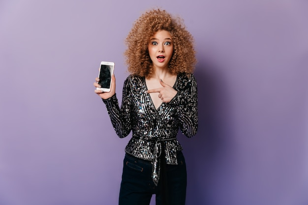 Donna desiderosa con occhi azzurri e capelli ricci vestita con una scintillante camicetta da discoteca indica smartphone.