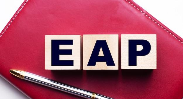 ペンの近くのバーガンディのノートに立つ木製の立方体で構成されたeap従業員支援プログラム