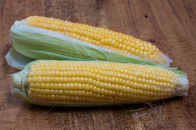 An ear of corn isolated on a wooden background