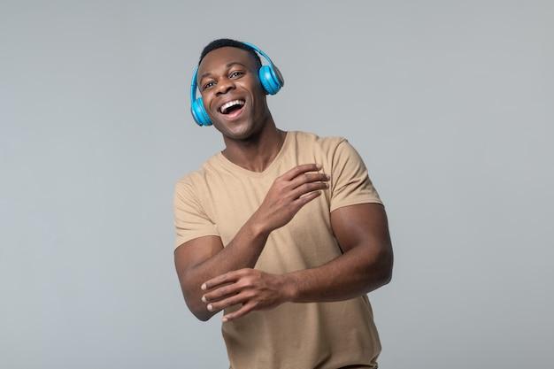 音楽の耳。スタジオで立っている開いた口を動かす手をヘッドフォンでエネルギッシュな幸せな若い暗い肌の男