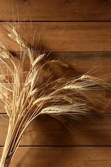 Ear golden wheat spike on wooden