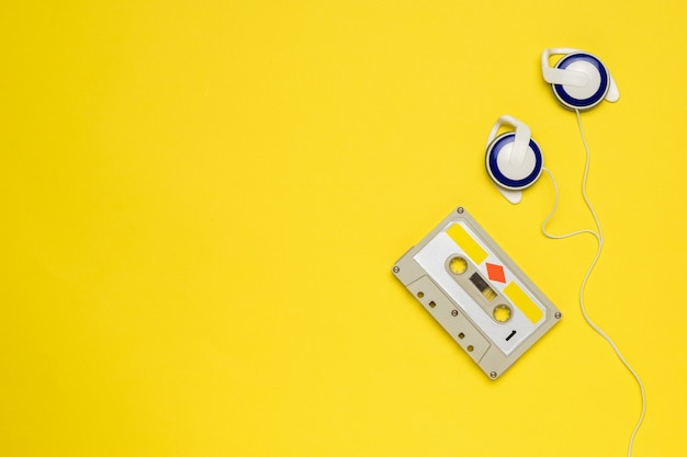 Over-ear headphones and a cassette with magnetic tape on yellow. vintage audio recording storage and playback tools.