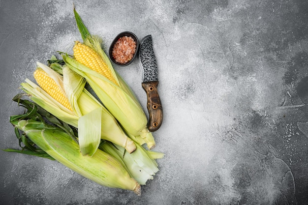 Ear of maize or corn set, on gray stone table background, top view flat lay, with copy space for text