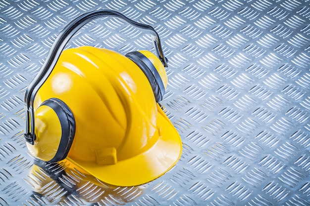 Ear muffs building helmet on grooved metal plate construction concept