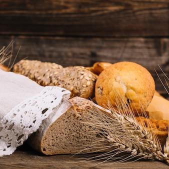 나무 테이블에 구운 빵과 밀의 귀