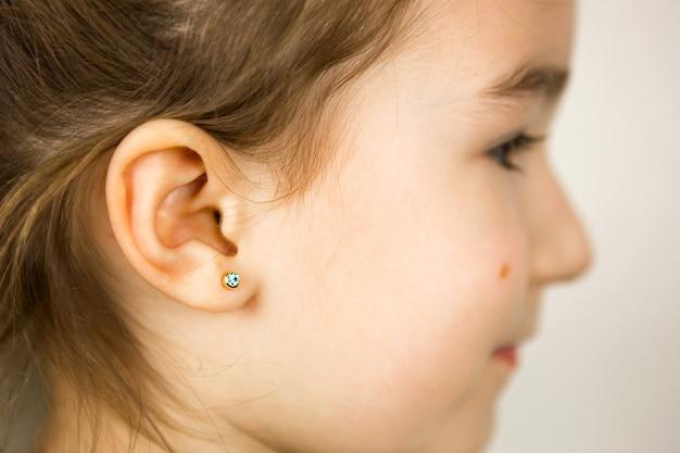 Прокол уха у ребенка - девочка показывает в ухе серьгу из медицинского сплава. белый фон, портрет девушки с родинкой на щеке в профиль.