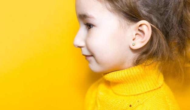 Прокол уха у ребенка - девочка показывает в ухе серьгу из медицинского сплава. желтый фон, портрет девушки в профиль.