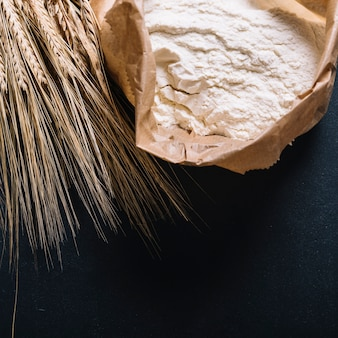 Ear of wheat and flour in paper bag on black background