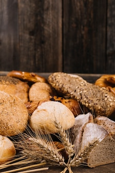 Ear of wheat in front of baked bread on wooden table