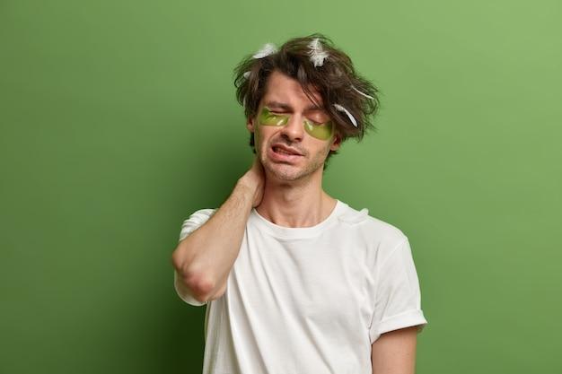 조기 각성 개념. 불쾌한 유럽인 남성은 수면 후 목 통증으로 고통 받고, 졸린 얼굴 표정을하고, 아침에 일어나서 콜라겐 패치, 불면증 및 수면 문제를 적용합니다.
