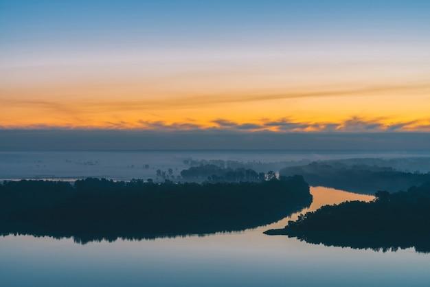 Рано голубое небо отражается в речной воде. берег реки с лесом под предрассветным небом. желтая полоса в живописном небе.
